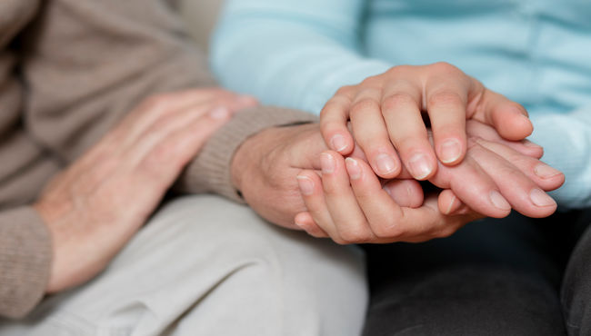 Two people comforting each other by  sitting and holding hands