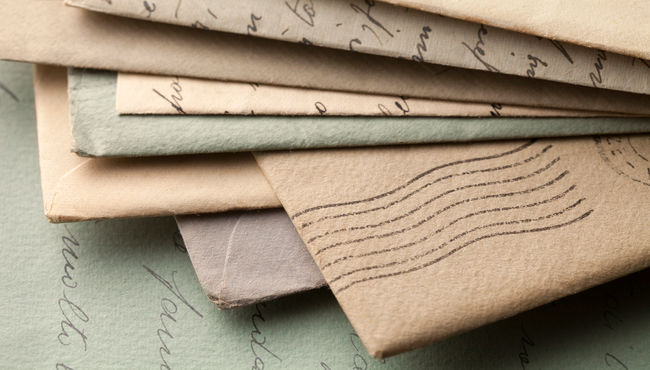 A pile of handwritten letters lying on top of an open letter.
